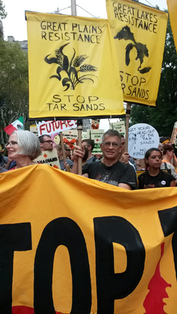 Protestors at the Climate March in NYC, 2014 holding 'stop tar sands' signs.