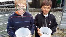 smiling boys with young salmon in buckets