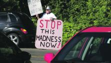 protester against Raven coal mine with signs